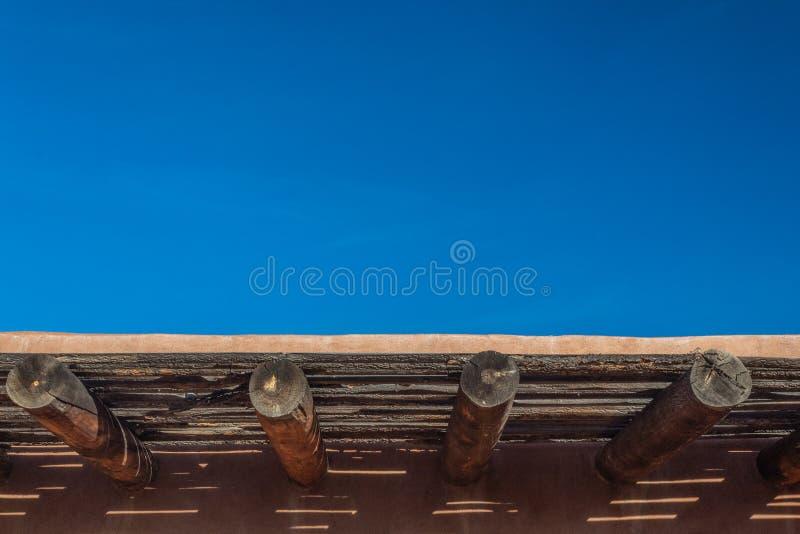 Céu azul vívido sobre a parede exterior do adôbe, vigas expostos, espaço da cópia foto de stock