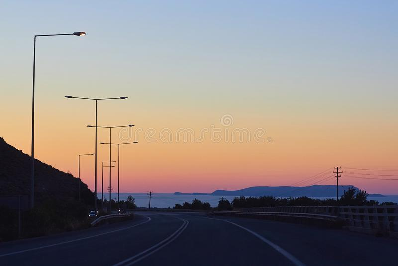 Céu bonito durante o por do sol, a estrada, a costa de mar e a silhueta da montanha fotos de stock