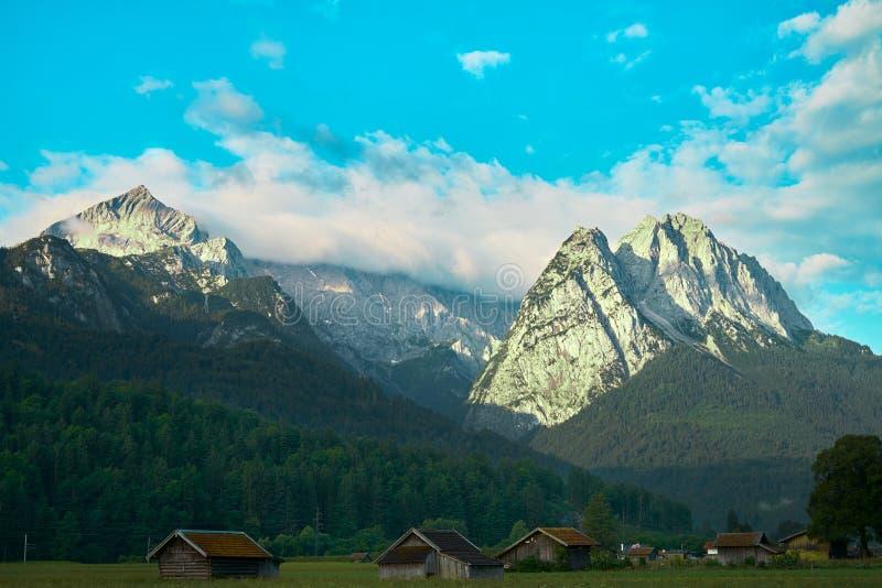 Céu branco-azul sobre Zugspitze com encostas de montanha arborizadas e um campo com cascos e galpões imagens de stock