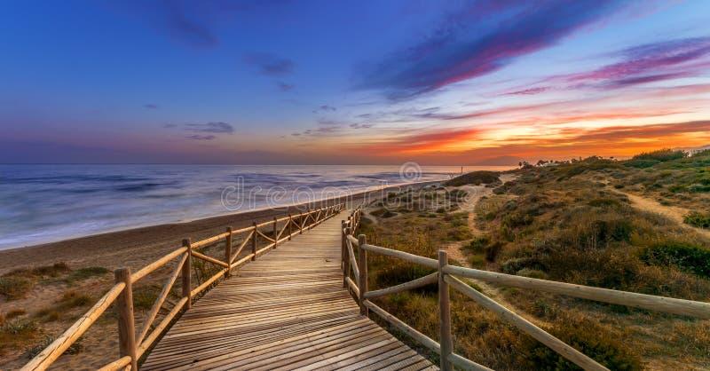 Céu brilhante do por do sol sobre o trajeto do mar e da madeira foto de stock royalty free