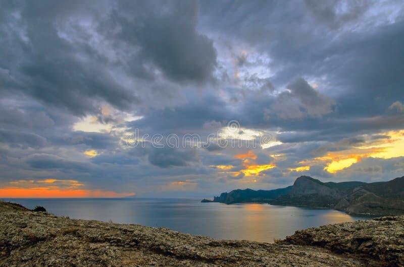 Céu cênico no por do sol sobre a baía em Sudak, no Mar Negro em Crimeia fotos de stock royalty free