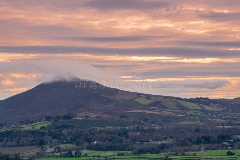 Céu cor-de-rosa e alaranjado sobre grande Sugar Loaf, condado Wicklow fotos de stock