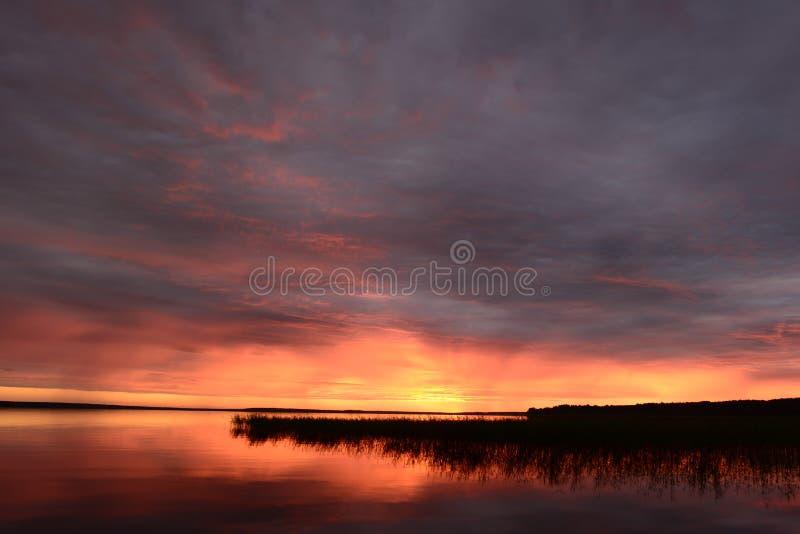 Céu crepuscular no fulgor de por do sol brilhante sobre a água calma do lago imagem de stock