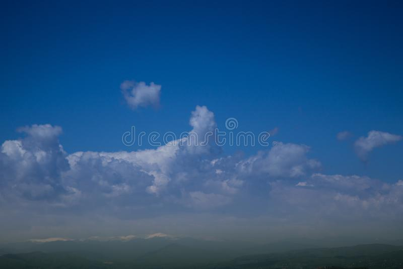 Céu de azuis marinhos com as nuvens sobre partes superiores da montanha fotos de stock