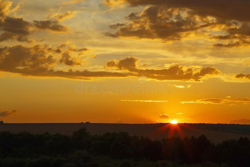 Céu de nivelamento dramático majestoso brilhante bonito na cor alaranjada do por do sol com raios O sol brilha sobre o horizonte  fotos de stock royalty free