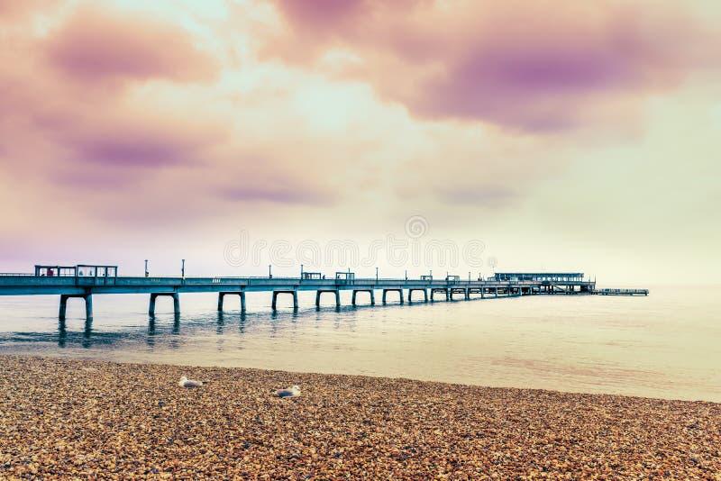 Céu de nivelamento dramático sobre o cais do negócio em Kent, Reino Unido Duas gaivotas estão sentando-se no Pebble Beach no prim foto de stock royalty free