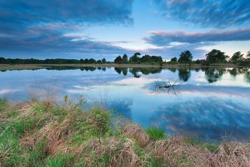 Céu do nascer do sol refletido no lago imagem de stock