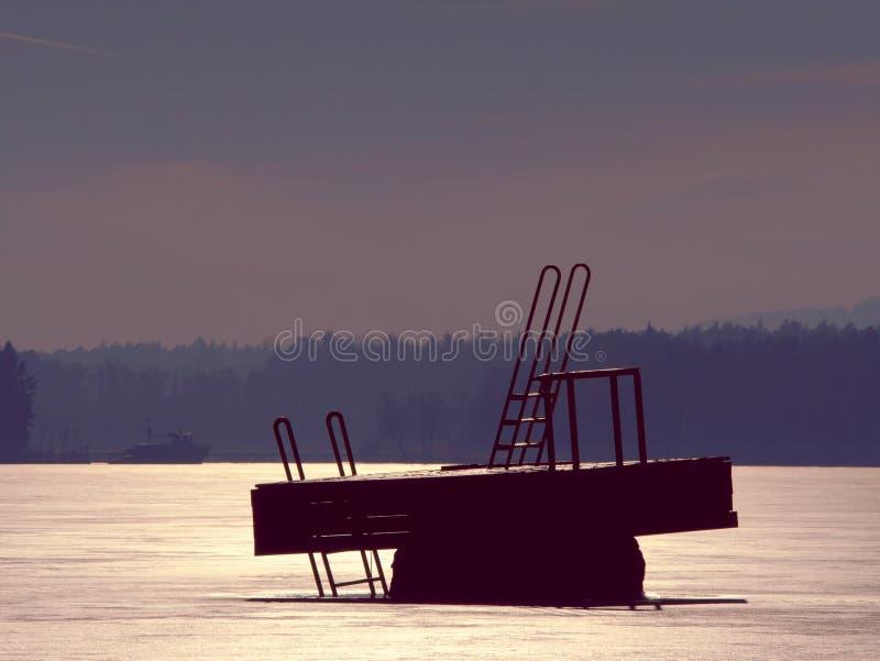 Céu do nascer do sol da beleza sobre o lago congelado da água entre montes foto de stock