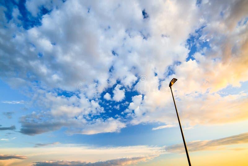 Céu do por do sol com nuvens e luz de rua macias imagem de stock