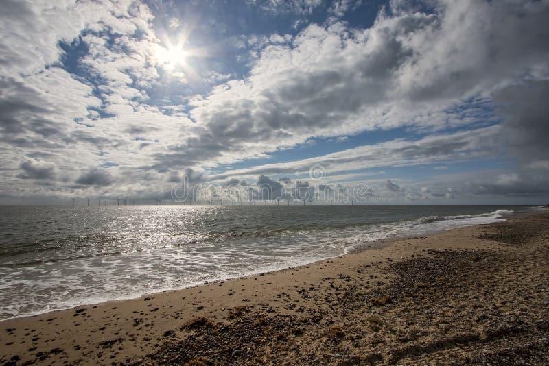 Céu dramático do tempo da costa Turbinas da explora??o agr?cola de vento a pouca dist?ncia do mar fotos de stock royalty free