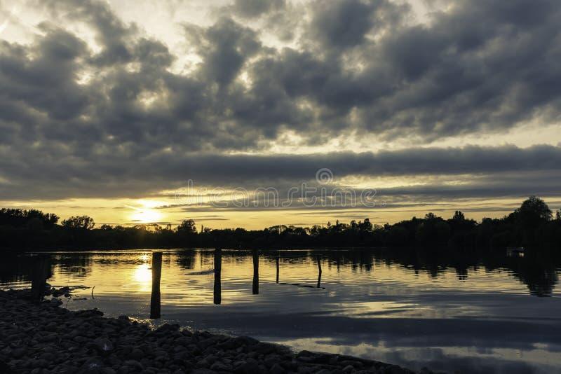 Céu dramático e por do sol sobre o lago foto de stock