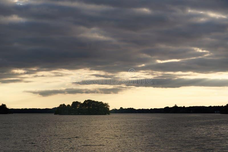 Céu dramático no por do sol sobre o lago com a floresta no horizonte foto de stock royalty free