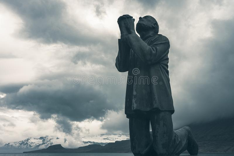 Céu dramático sobre vítimas da estátua Eskifjordur do mar, Islândia foto de stock royalty free