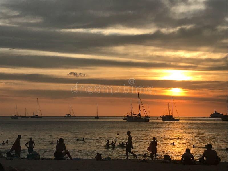 Céu e praia bonitos do oceano quando por do sol e povos na praia imagens de stock royalty free