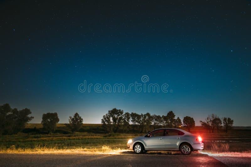 Céu estrelado da noite acima do país Asphalt Road In Countryside Estacionamento do carro do sedan perto de Asphalt Road fotos de stock royalty free