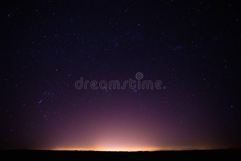 Céu estrelado da noite colorida acima da cidade amarela fotos de stock