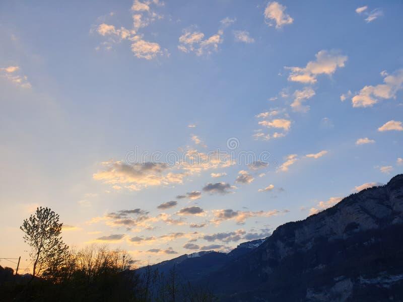 Céu nebuloso, azul e esbranquiçado profundos sobre a montanha e o lago foto de stock