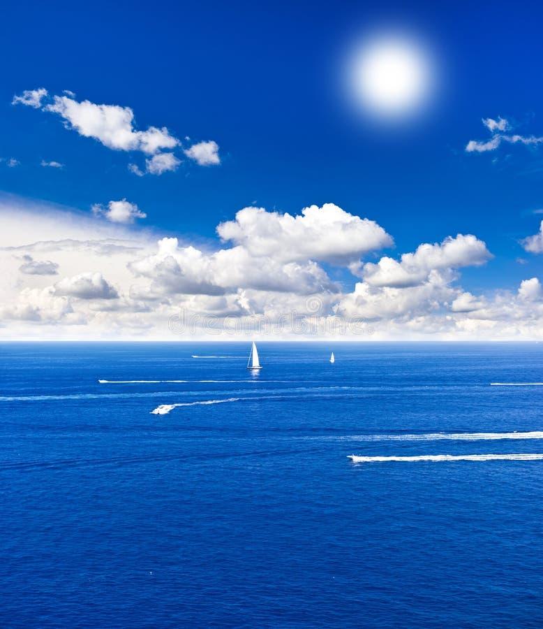 Céu nebuloso com sol. mar azul bonito. fotografia de stock royalty free