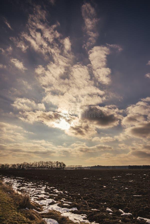 Céu nebuloso dramático sobre a paisagem adiantada da mola com campo fotografia de stock royalty free