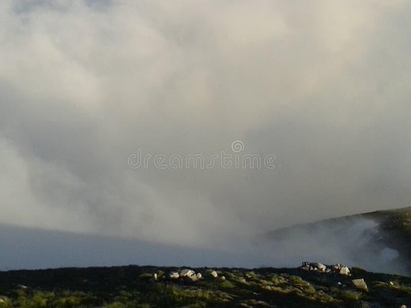 Céu nebuloso no por do sol sobre a parte superior da montanha foto de stock royalty free