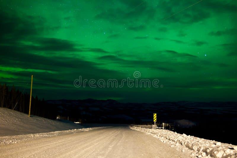 Céu nocturno da aurora boreal sobre a estrada rural do inverno imagens de stock royalty free