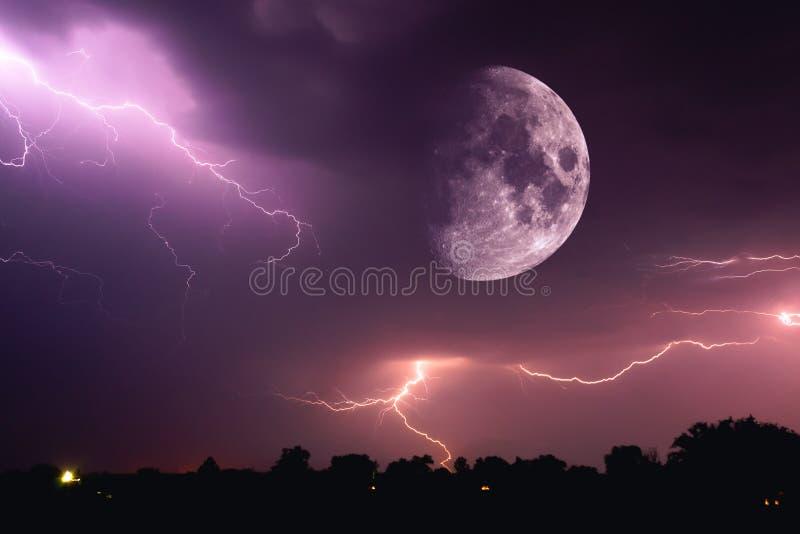 Céu noturno de Dia das Bruxas com nuvens e flashes de relâmpago e de um close up vermelho ensanguentado emergente da Lua cheia na foto de stock royalty free