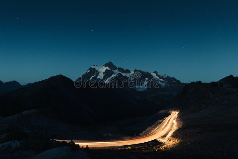 Céu noturno de surpresa com montanhas rochosas nevados no meio e em uma estrada não ofuscante leve foto de stock