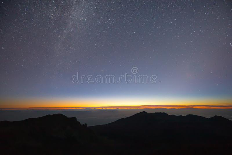 Céu noturno do vulcão de Haleakala com Via Látea e nascer do sol acima das nuvens fotografia de stock royalty free