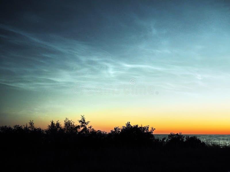 Céu noturno e nuvens Noctilucent sobre o mar foto de stock royalty free