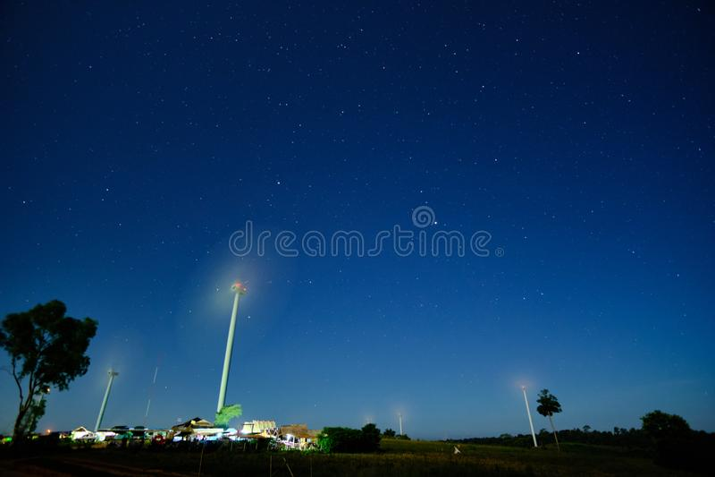 Céu noturno estrelado sobre os campos da turbina eólica no primeiro plano fotos de stock royalty free