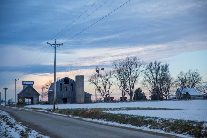 Céu obscuro do inverno nebuloso sobre a exploração agrícola e o moinho de vento abandonados velhos fotos de stock