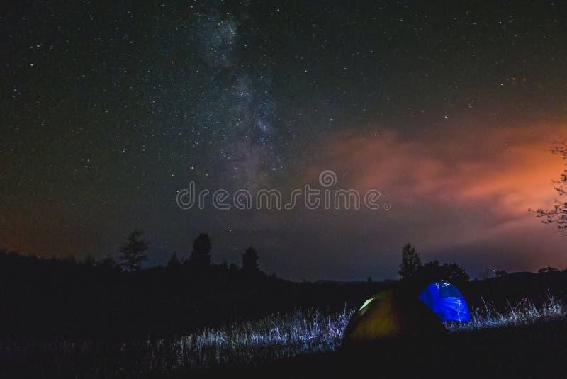 Céu surrealista sobre duas barracas na noite, na Via Látea e nas nuvens fotografia de stock royalty free