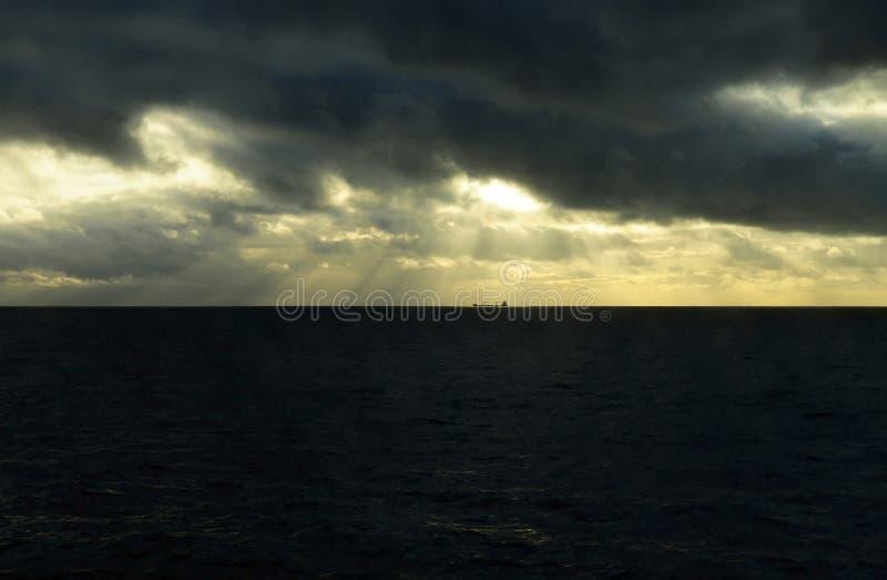 Céu tormentoso escuro com raios dourados da luz do sol, navio de carga imagens de stock royalty free