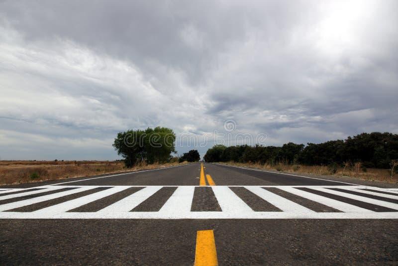 Céu tormentoso sobre a estrada rural fotografia de stock