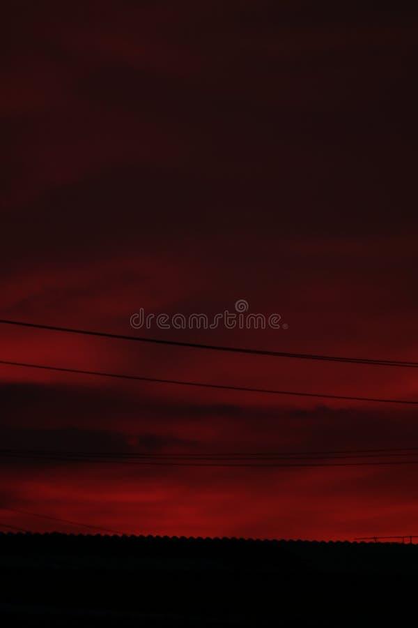 Céu vermelho na noite e fio no telhado fotografia de stock royalty free