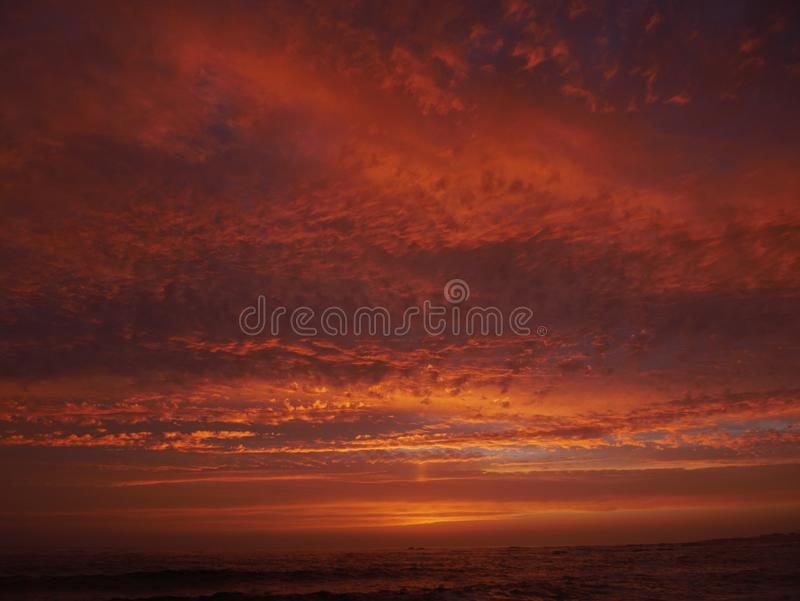 Céu vermelho vívido no por do sol na praia com nuvens dramáticas e o mar escuro fotos de stock