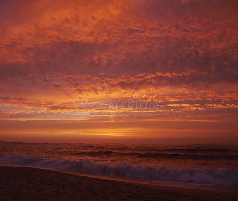 Céu vermelho vívido no por do sol na praia com oceano escuro fotografia de stock royalty free