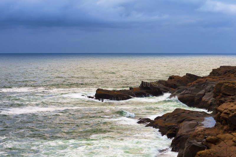 Céus de escurecimento da tempestade ao longo das costas litorais rochosas imagem de stock