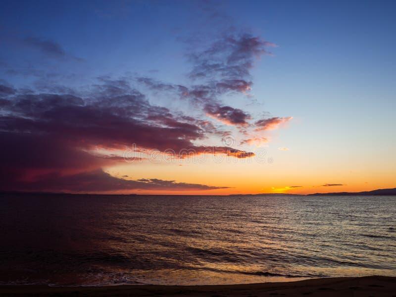 Céus e nuvens de surpresa sobre uma praia vazia bonita - tiro do por do sol foto de stock royalty free