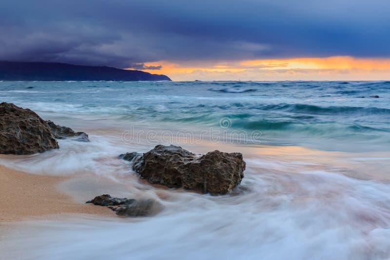 Céus no fogo no por do sol, com a chuva no fundo na costa norte em Oahu, Havaí fotos de stock royalty free