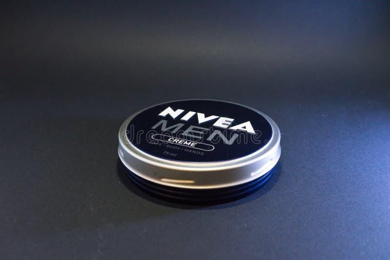 Círculo clássico da nata dos homens de Nivea para o corpo da cara e recipiente das mãos no fundo preto isolado fotos de stock royalty free