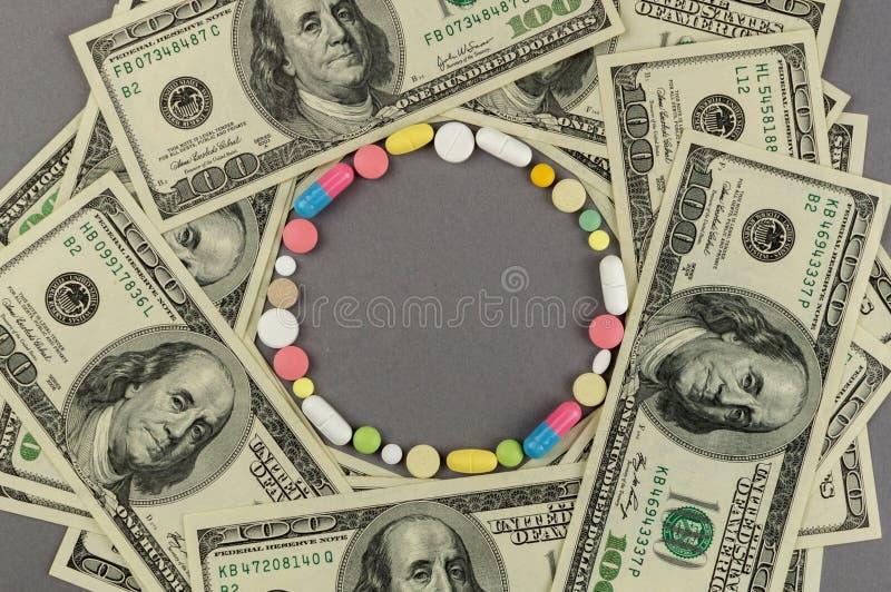 Círculo criado dos comprimidos coloridos com o dinheiro Conceito MÉDICO fotografia de stock royalty free
