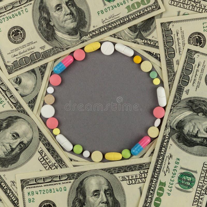 Círculo criado dos comprimidos coloridos com o dinheiro Conceito MÉDICO foto de stock royalty free