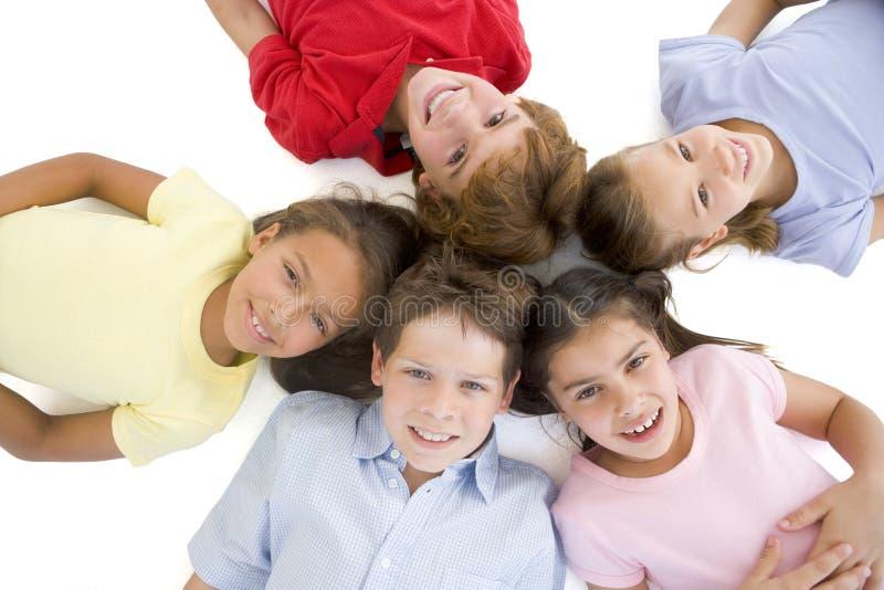 Círculo de la sonrisa joven de cinco amigos foto de archivo libre de regalías