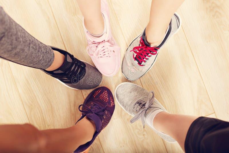 Círculo de piernas con los zapatos en un gimnasio imagenes de archivo