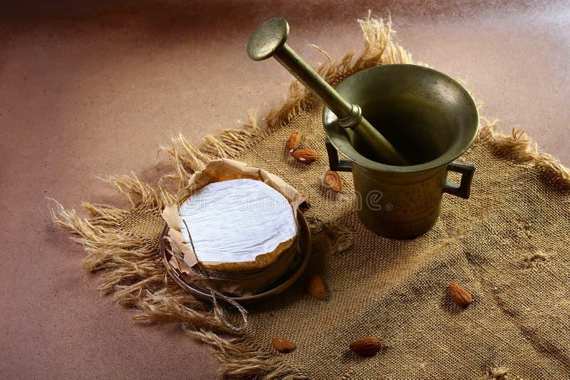 Círculo do queijo do camembert ou do brie da amêndoa no papel de embalagem marrom decorado, prato da especiaria na tela áspera ve fotos de stock