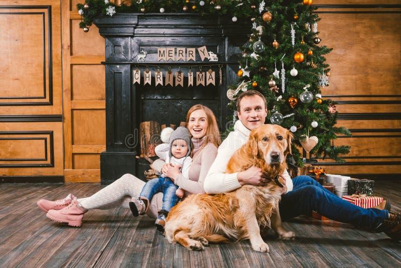 Círculo familiar de la Navidad del tema y del Año Nuevo Familia caucásica joven con el golden retriever de 1 año de Labrador de l imagen de archivo