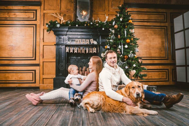 Círculo familiar de la Navidad del tema y del Año Nuevo Familia caucásica joven con el golden retriever de 1 año de Labrador de l fotografía de archivo libre de regalías