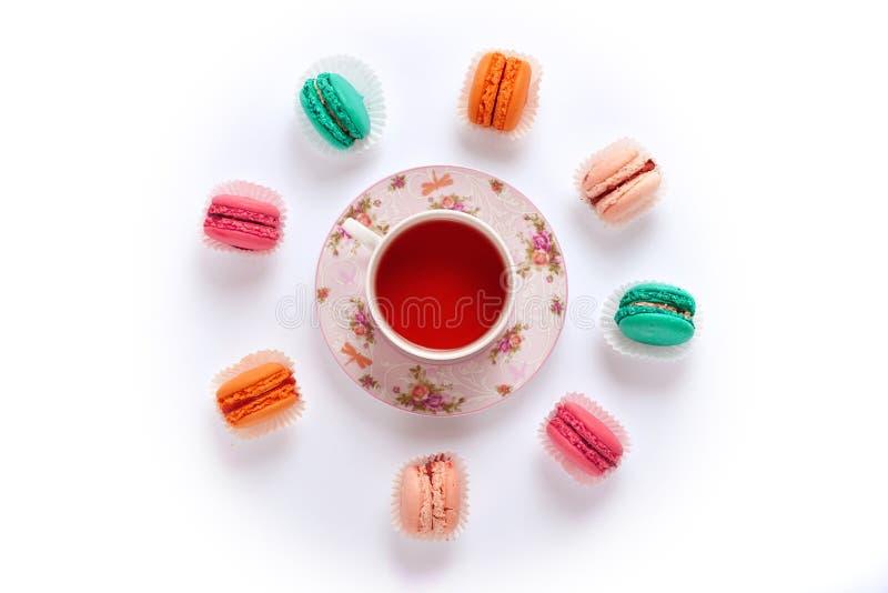 Círculo y té de los macarrones en un fondo blanco desde arriba fotografía de archivo