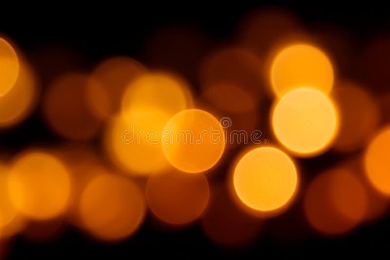 Círculos alaranjados de Bokeh no fundo preto para Dia das Bruxas imagem de stock royalty free